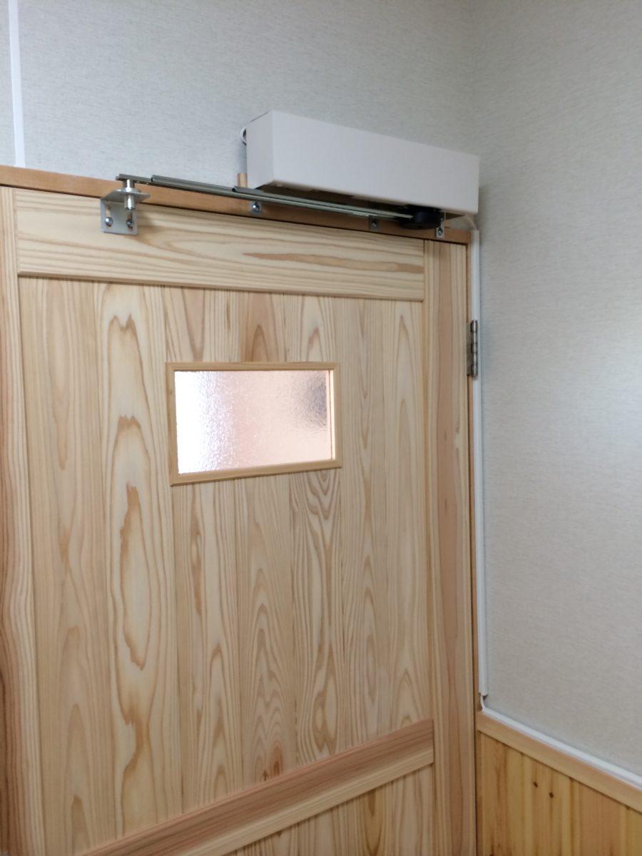 老人介護施設の開き戸トイレを自動化